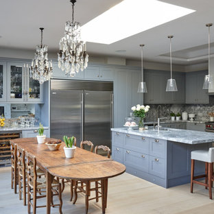 Photo of a large classic u-shaped kitchen/diner in London with shaker cabinets, grey cabinets, grey splashback, stone slab splashback, light hardwood flooring, an island, beige floors and grey worktops.