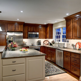 Inspiration for a mid-sized traditional u-shaped eat-in kitchen in Philadelphia with a double-bowl sink, raised-panel cabinets, dark wood cabinets, laminate benchtops, white splashback, porcelain splashback, stainless steel appliances, light hardwood floors and with island.