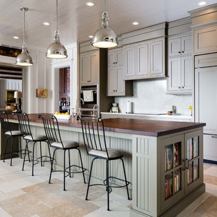 Photo of a mid-sized transitional single-wall eat-in kitchen in Nashville with a farmhouse sink, flat-panel cabinets, green cabinets, wood benchtops, white splashback, panelled appliances, slate floors and with island.