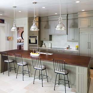 Large country kitchen in Nashville with a farmhouse sink, recessed-panel cabinets, green cabinets, wood benchtops, stainless steel appliances, with island, beige floor and slate floors.