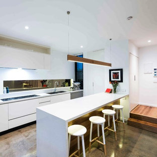 Inspiration for a medium sized contemporary single-wall open plan kitchen in Melbourne with concrete flooring, a double-bowl sink, flat-panel cabinets, white cabinets, granite worktops, metallic splashback, mirror splashback, black appliances and an island.