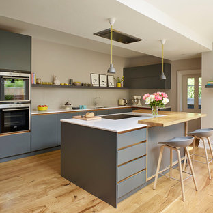 Photo of a large scandi l-shaped kitchen in London with flat-panel cabinets, grey cabinets, composite countertops, beige splashback, light hardwood flooring, an island, beige floors, white worktops, a submerged sink, glass sheet splashback and stainless steel appliances.