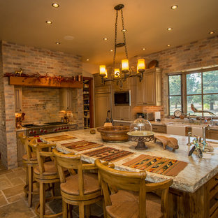 Inspiration for an expansive country eat-in kitchen in Denver with a farmhouse sink, distressed cabinets, granite benchtops, stainless steel appliances, travertine floors, with island, louvered cabinets, red splashback and stone tile splashback.