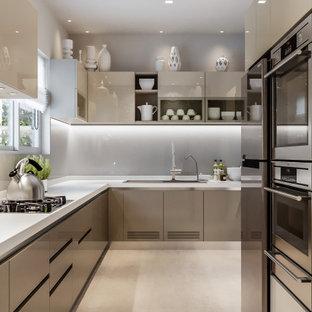 Imagen de cocina en U, contemporánea, de tamaño medio, con fregadero encastrado, armarios con paneles lisos, puertas de armario grises, salpicadero verde, salpicadero de vidrio templado, electrodomésticos de acero inoxidable, suelo beige y encimeras turquesas