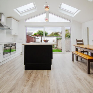 Photo of a mid-sized contemporary galley eat-in kitchen in Dublin with a drop-in sink, louvered cabinets, white cabinets, laminate benchtops, white splashback, black appliances, laminate floors, a peninsula, brown floor and white benchtop.
