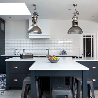 Mid-sized transitional l-shaped kitchen in Other with shaker cabinets, blue cabinets, quartzite benchtops, white splashback, ceramic splashback, ceramic floors, with island, an undermount sink and grey floor.