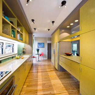 Inredning av ett modernt avskilt, stort parallellkök, med släta luckor, gula skåp, grönt stänkskydd, rostfria vitvaror, en undermonterad diskho, bänkskiva i återvunnet glas, stänkskydd i glaskakel, ljust trägolv och brunt golv