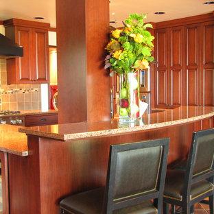 Diseño de cocina en U, clásica, abierta, con fregadero bajoencimera, puertas de armario de madera oscura y encimera de granito