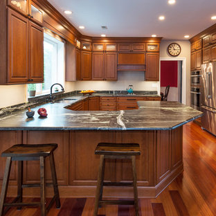 This is an example of a large traditional u-shaped eat-in kitchen in Philadelphia with an undermount sink, raised-panel cabinets, medium wood cabinets, soapstone benchtops, black splashback, stone slab splashback, stainless steel appliances, medium hardwood floors and a peninsula.