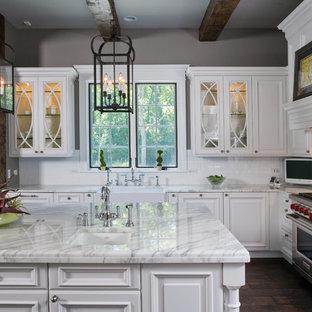 Неиссякаемый источник вдохновения для домашнего уюта: огромная п-образная кухня-гостиная в классическом стиле с раковиной в стиле кантри, фасадами с выступающей филенкой, белыми фасадами, мраморной столешницей, белым фартуком, фартуком из керамической плитки, техникой под мебельный фасад, темным паркетным полом и островом