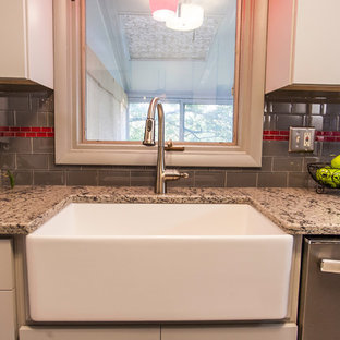 Photo of a small eclectic galley separate kitchen in Baltimore with a farmhouse sink, flat-panel cabinets, grey cabinets, granite benchtops, multi-coloured splashback, subway tile splashback, stainless steel appliances, no island, vinyl floors and grey floor.