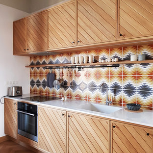 This is an example of an eclectic kitchen in Other with an integrated sink, louvered cabinets, medium wood cabinets, multi-coloured splashback, mosaic tile splashback, black appliances, light hardwood floors and beige floor.