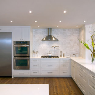 Design ideas for a large transitional l-shaped open plan kitchen in Portland with quartz benchtops, white splashback, white cabinets, shaker cabinets, stainless steel appliances, an undermount sink, marble splashback, medium hardwood floors, brown floor and with island.