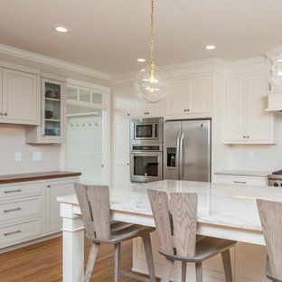 Large transitional eat-in kitchen pictures - Inspiration for a large transitional u-shaped medium tone wood floor and brown floor eat-in kitchen remodel in Raleigh with a farmhouse sink, shaker cabinets, white cabinets, white backsplash, stainless steel appliances, an island, quartzite countertops, subway tile backsplash and white countertops