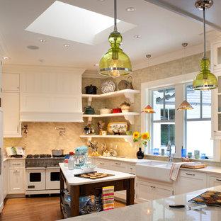 Mittelgroße Klassische Wohnküche in U-Form mit Schrankfronten im Shaker-Stil, Landhausspüle, Elektrogeräten mit Frontblende, weißen Schränken, Arbeitsplatte aus Terrazzo, Küchenrückwand in Gelb, Rückwand aus Keramikfliesen, braunem Holzboden, Kücheninsel und Mauersteinen in Sonstige