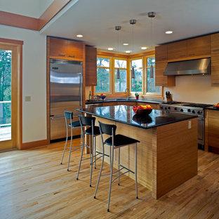 Mittelgroße Klassische Wohnküche in L-Form mit Unterbauwaschbecken, flächenbündigen Schrankfronten, hellen Holzschränken, Onyx-Arbeitsplatte, Küchenrückwand in Beige, Küchengeräten aus Edelstahl, hellem Holzboden und Kücheninsel in Seattle