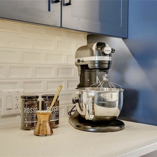 Design ideas for a small contemporary galley kitchen/diner in Calgary with a double-bowl sink, recessed-panel cabinets, blue cabinets, quartz worktops, white splashback, marble splashback, stainless steel appliances, plywood flooring, an island, multi-coloured floors and white worktops.