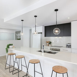 Mid-sized contemporary galley kitchen in Other with white splashback, flat-panel cabinets, ceramic splashback, light hardwood floors, white benchtop, an undermount sink, white cabinets, white appliances, with island and beige floor.