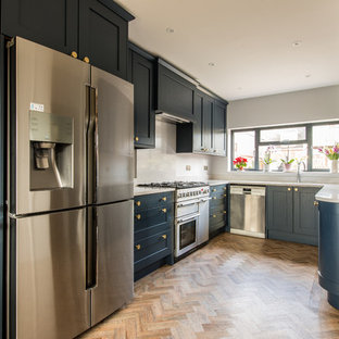 Medium sized classic u-shaped kitchen in Kent with recessed-panel cabinets, blue cabinets, quartz worktops, light hardwood flooring, no island, beige floors and white worktops.