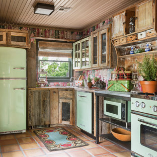 This is an example of a rustic l-shaped kitchen in Other with glass-front cabinets, distressed cabinets, wood worktops, multi-coloured splashback, coloured appliances and terracotta flooring.