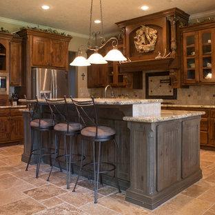 オースティンの中サイズのラスティックスタイルのおしゃれなキッチン (シェーカースタイル扉のキャビネット、濃色木目調キャビネット、御影石カウンター、ベージュキッチンパネル、石タイルのキッチンパネル、シルバーの調理設備の、トラバーチンの床、ベージュの床) の写真