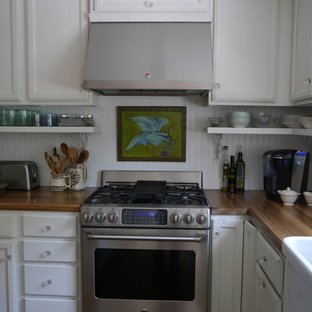 Inspiration for a mid-sized cottage u-shaped medium tone wood floor open concept kitchen remodel in DC Metro with a farmhouse sink, recessed-panel cabinets, distressed cabinets, wood countertops, white backsplash, stainless steel appliances and an island