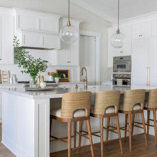 サクラメントの広いトランジショナルスタイルのおしゃれなキッチン (エプロンフロントシンク、シェーカースタイル扉のキャビネット、白いキャビネット、クオーツストーンカウンター、白いキッチンパネル、セラミックタイルのキッチンパネル、シルバーの調理設備、無垢フローリング、茶色い床、グレーのキッチンカウンター、三角天井) の写真