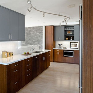 Contemporary kitchen pictures - Example of a trendy light wood floor kitchen design in San Francisco with flat-panel cabinets, gray cabinets, an undermount sink, white backsplash and porcelain backsplash