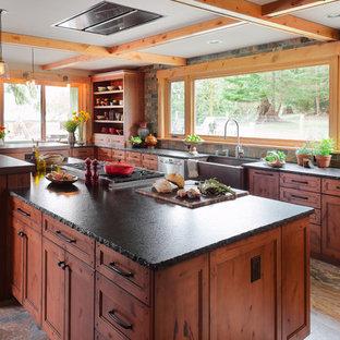 Foto på ett mellanstort rustikt parallellkök, med en rustik diskho, skåp i mellenmörkt trä, granitbänkskiva, grått stänkskydd, stänkskydd i skiffer, rostfria vitvaror, klinkergolv i porslin, en köksö, grått golv och luckor med infälld panel