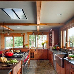 Geschlossene, Mittelgroße Urige Küche in L-Form mit Landhausspüle, Schrankfronten im Shaker-Stil, hellbraunen Holzschränken, Granit-Arbeitsplatte, Küchenrückwand in Grau, Rückwand aus Schiefer, Küchengeräten aus Edelstahl, Porzellan-Bodenfliesen, Kücheninsel und grauem Boden in Seattle