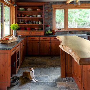 Inspiration for a medium sized country l-shaped enclosed kitchen in Seattle with a belfast sink, shaker cabinets, medium wood cabinets, granite worktops, grey splashback, slate splashback, stainless steel appliances, porcelain flooring, an island and grey floors.