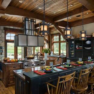 This is an example of a large rustic kitchen in Calgary with a belfast sink, granite worktops, stainless steel appliances, medium hardwood flooring, multiple islands and black cabinets.
