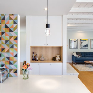Ispirazione per una cucina minimalista di medie dimensioni con ante lisce, ante bianche, top in quarzo composito, paraspruzzi multicolore, paraspruzzi con piastrelle di cemento, isola e pavimento marrone