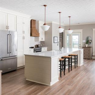 Inspiration för ett mellanstort vintage grå grått kök med öppen planlösning, med skåp i shakerstil, vita skåp, bänkskiva i kvarts, vitt stänkskydd, rostfria vitvaror, mellanmörkt trägolv, en köksö, en rustik diskho och brunt golv
