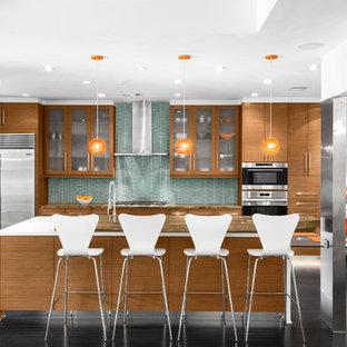 ヒューストンの中サイズのコンテンポラリースタイルのおしゃれなキッチン (フラットパネル扉のキャビネット、中間色木目調キャビネット、緑のキッチンパネル、シルバーの調理設備の、濃色無垢フローリング、アンダーカウンターシンク、御影石カウンター、ガラス板のキッチンパネル、茶色い床) の写真