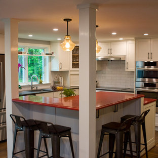 Inspiration for a mid-sized eclectic l-shaped eat-in kitchen in Boston with an undermount sink, recessed-panel cabinets, white cabinets, quartz benchtops, white splashback, subway tile splashback, stainless steel appliances, porcelain floors, with island, brown floor and red benchtop.