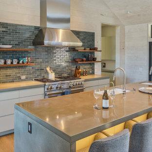 サンフランシスコの巨大なカントリー風おしゃれなキッチン (アンダーカウンターシンク、フラットパネル扉のキャビネット、白いキャビネット、コンクリートカウンター、シルバーの調理設備、青いキッチンパネル、無垢フローリング、茶色い床) の写真