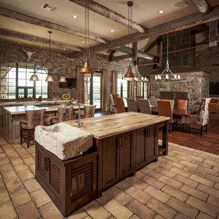Cette photo montre une grand cuisine ouverte montagne en L avec des portes de placard en bois sombre, un évier posé, un placard à porte shaker, un plan de travail en bois, une crédence multicolore, une crédence en brique, un sol en brique, 2 îlots et un sol beige.