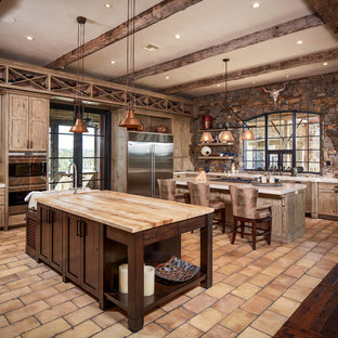 This is an example of a large country l-shaped eat-in kitchen in Houston with a farmhouse sink, raised-panel cabinets, light wood cabinets, wood benchtops, multi-coloured splashback, brick splashback, stainless steel appliances, brick floors, multiple islands and beige floor.