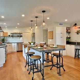 サンディエゴの大きいインダストリアルスタイルのおしゃれなキッチン (シングルシンク、シェーカースタイル扉のキャビネット、白いキャビネット、クオーツストーンカウンター、白いキッチンパネル、サブウェイタイルのキッチンパネル、シルバーの調理設備の、淡色無垢フローリング、茶色い床) の写真