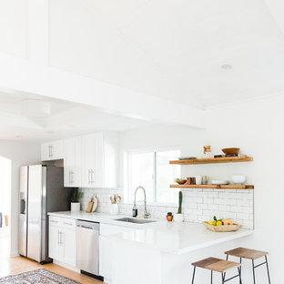 На фото: кухня в скандинавском стиле с одинарной раковиной, фасадами в стиле шейкер, белыми фасадами, столешницей из кварцита, белым фартуком, фартуком из плитки кабанчик, техникой из нержавеющей стали и полом из бамбука с