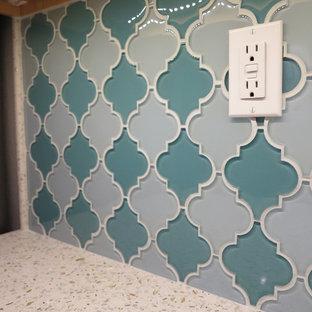 ロサンゼルスの中サイズのコンテンポラリースタイルのおしゃれなキッチン (アンダーカウンターシンク、レイズドパネル扉のキャビネット、中間色木目調キャビネット、クオーツストーンカウンター、青いキッチンパネル、ガラスタイルのキッチンパネル、シルバーの調理設備の、無垢フローリング、アイランドなし) の写真