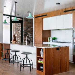 タンパの中サイズのコンテンポラリースタイルのおしゃれなキッチン (エプロンフロントシンク、フラットパネル扉のキャビネット、中間色木目調キャビネット、御影石カウンター、白いキッチンパネル、石スラブのキッチンパネル、シルバーの調理設備、茶色い床、マルチカラーのキッチンカウンター、無垢フローリング) の写真