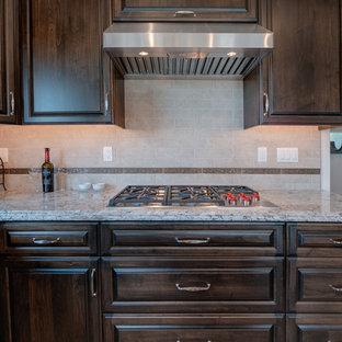 Ispirazione per una cucina chic di medie dimensioni con lavello sottopiano, ante con bugna sagomata, ante in legno bruno, top in granito, paraspruzzi beige, paraspruzzi in gres porcellanato, elettrodomestici in acciaio inossidabile, isola e top multicolore