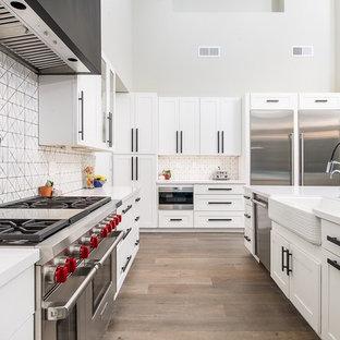 Inspiration för stora klassiska kök, med en rustik diskho, vita skåp, vitt stänkskydd, rostfria vitvaror, ljust trägolv, en köksö, skåp i shakerstil, bänkskiva i koppar och stänkskydd i keramik