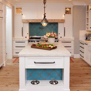 Idee per una cucina ad U mediterranea con ante bianche, top in marmo, paraspruzzi bianco e top bianco