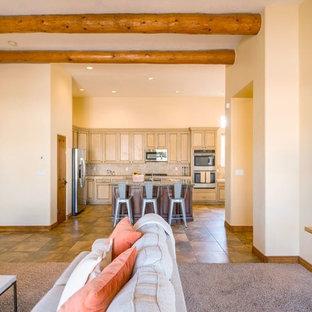 他の地域の中サイズのサンタフェスタイルのおしゃれなキッチン (シングルシンク、黄色いキャビネット、御影石カウンター、ベージュキッチンパネル、石タイルのキッチンパネル、シルバーの調理設備、トラバーチンの床、茶色い床) の写真