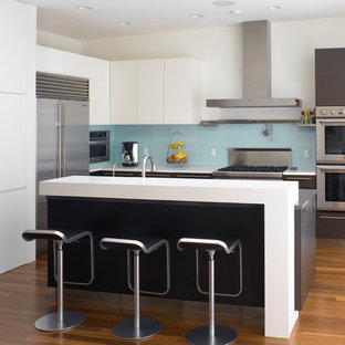 Large modern kitchen ideas - Inspiration for a large modern l-shaped dark wood floor and brown floor kitchen remodel in San Francisco with flat-panel cabinets, blue backsplash, glass sheet backsplash, stainless steel appliances, an island, an undermount sink, white cabinets and quartz countertops