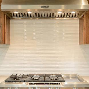 Пример оригинального дизайна: п-образная кухня-гостиная среднего размера в современном стиле с одинарной раковиной, плоскими фасадами, темными деревянными фасадами, столешницей из кварцевого композита, белым фартуком, фартуком из цементной плитки, техникой из нержавеющей стали, полом из бамбука и островом