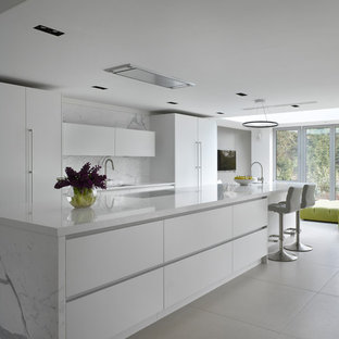 Design ideas for a large contemporary galley open plan kitchen in London with flat-panel cabinets, white cabinets, composite countertops, white splashback, marble splashback, integrated appliances, an island, white worktops, a submerged sink and grey floors.